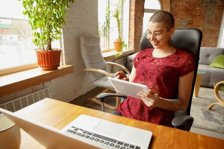 Happy Woman working from home during coronavirus or COVID-19 quarantine, remote office concept. Beautiful bald model, manager doing tasks with laptop, phone, has online conference, meeting. Banco de Imagens