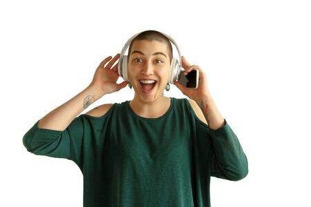 Listening to music. Portrait of young caucasian woman with freaky appearance on white background. Unusual look with tattoos and bald. Human emotions, facial expression,sales, ad concept. Youth culture. 版權商用圖片