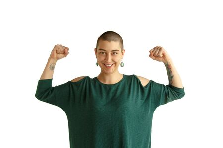 Be strong. Portrait of young caucasian woman with freaky appearance on white background. Unusual look with tattoos and bald. Human emotions, facial expression,sales, ad concept. Youth culture. 免版税图像