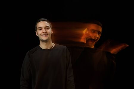 Smiles outside, laughting inside. The versatility of man - opened emotions and hidden feelings. Caucasian man on black background with different faces of condition. Double exposure. Mental health.