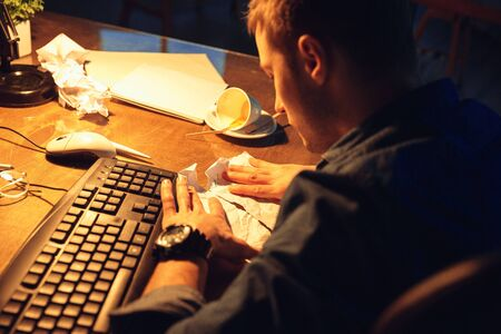 Going crazy. Man working in office alone during coronavirus or COVID-19 quarantine, staying to late night. Young businessman, manager doing tasks with smartphone, laptop, tablet in empty workspace.