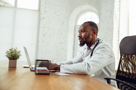 Doctor consulting for patient online, giving recommendation. African-american doctor during his work, explaining recipes for drug. Daily hard work for health and lives saving during epidemic.