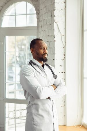 Doctor posing confident in his cabinet near window. African-american doctor during his work with patients, explaining recipes for drug. Daily hard work for health and lives saving during epidemic.