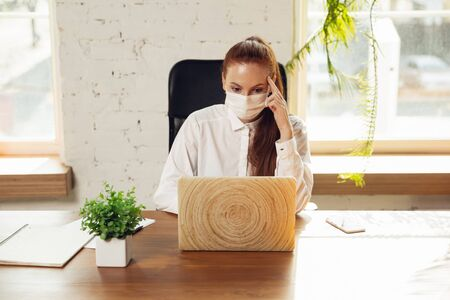 Woman working in office alone during coronavirus or COVID-19 quarantine, wearing face mask.