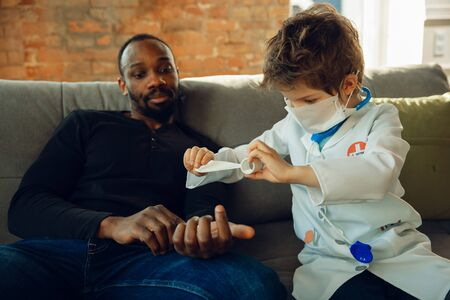Caucasian teenboy as a doctor consulting for patient at home, giving recommendation, treating. Little doctor giving vaccine, taking care. Concept of childhood, human emotions, health, medicine. Stockfoto