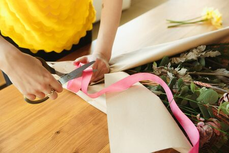 Florist at work: woman shows how to make bouquet. Young caucasian woman gives online workshop of doing gift, present for celebration, with computer. Working at home while isolated, quarantined concept.