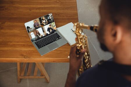 African-american musician playing saxophone during online concert at home isolated and quarantined. Using camera, laptop, streaming, recording courses. Concept of art, support, music, hobby, education.