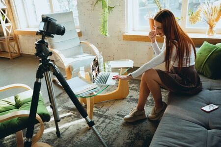 Caucasian woman singing during online concert at home isolated and quarantined. Using camera, laptop, streaming, recording courses, dancing. Concept of art, support, music, hobby, education.
