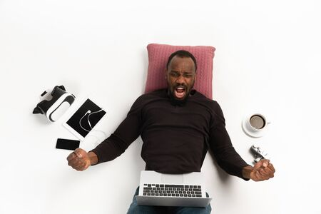 Young african-american man using devices, gadgets isolated on white studio background. Concept of modern technologies, gadgets, tech, emotions, ad. Copyspace. Gaming, shopping, meeting online education.