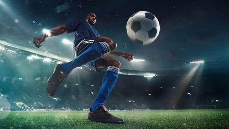 Professioneller Fußball- oder Fußballspieler in Aktion im Stadion mit Taschenlampen, Kickball zum Siegtor, Weitwinkel. Konzept von Sport, Wettbewerb, Bewegung, Überwindung. Feldpräsenzeffekt.