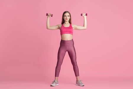 Fiducia. Bella giovane atleta femminile che pratica in studio, ritratto rosa monocromatico. Modello caucasico dalla vestibilità sportiva con pesi. Body building, stile di vita sano, bellezza e concetto di azione.