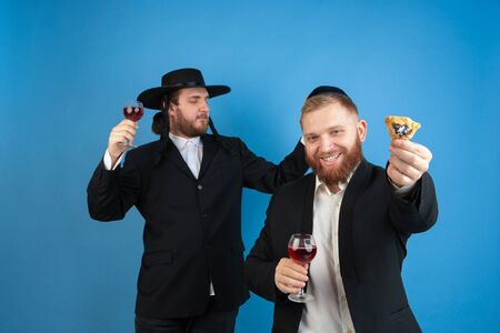 Dancing with wine, having fun. Portrait of a young orthodox jewish men isolated on blue studio background. Purim, business, festival, holiday, celebration Pesach or Passover, judaism, religion concept.