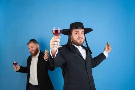 Dancing with wine, having fun. Portrait of a young orthodox jewish men isolated on blue studio background. Purim, business, festival, holiday, celebration Pesach or Passover, judaism, religion concept. Stock Photo
