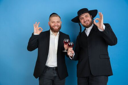 Dancing with wine. Portrait of a young orthodox jewish men isolated on blue studio background. Purim, business, festival, holiday, celebration Pesach or Passover, judaism, religion concept.