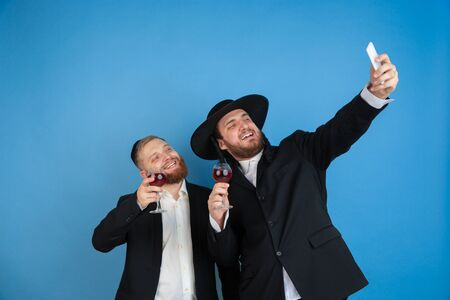 Taking selfie with wine. Portrait of a young orthodox jewish men isolated on blue studio background. Purim, business, festival, holiday, celebration Pesach or Passover, judaism, religion concept.