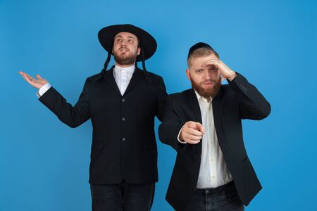 Pointing, choosing. Portrait of a young orthodox jewish men isolated on blue studio background. Purim, business, festival, holiday, celebration Pesach or Passover, judaism, religion concept.