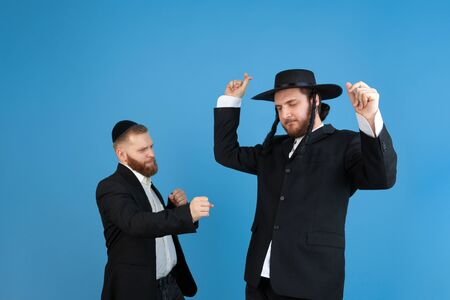Dancing, having fun. Portrait of a young orthodox jewish men isolated on blue studio background. Purim, business, festival, holiday, celebration Pesach or Passover, judaism, religion concept.