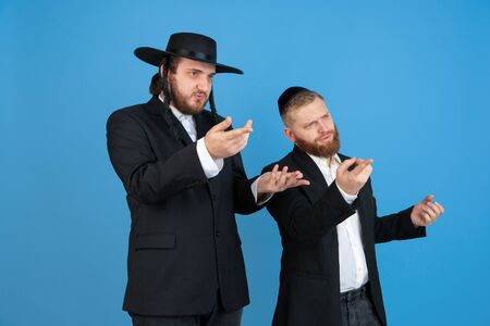 Pointing, asking. Portrait of a young orthodox jewish men isolated on blue studio background. Purim, business, festival, holiday, celebration Pesach or Passover, judaism, religion concept. Stock Photo