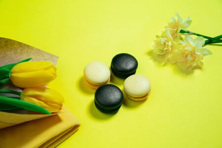 Macaroons and flowers. Monochrome stylish and trendy composition in yellow color on studio background. Top view, flat lay. Pure beauty of usual things around. Copyspace for ad. Holiday, food, fashion.