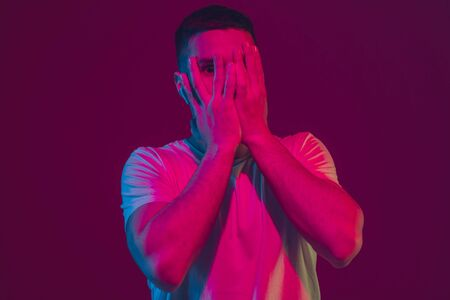 Scared hiding face. Caucasian mans portrait isolated on pink-purple studio background in neon light. Beautiful male model with earphones. Concept of human emotions, facial expression, sales, ad.