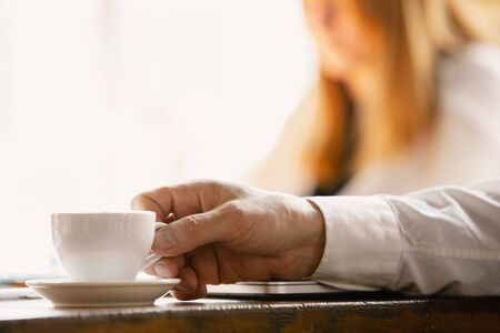 Holding coffee cup. Close up of caucasian male hands, working in office. Concept of business, finance, job, online shopping or sales. Copyspace for advertising. Education, communication freelance.