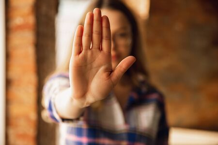 Close up view of young woman making stop gesture with her hand. Cropped isolated portrait of caucasian female model. Showing her position, rejecting, defending. Copyspace for advertising.