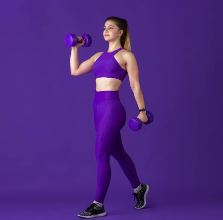 Happy. Beautiful young female athlete practicing in studio, monochrome purple portrait. Sportive fit caucasian model with weights. Body building, healthy lifestyle, beauty and action concept. Standard-Bild