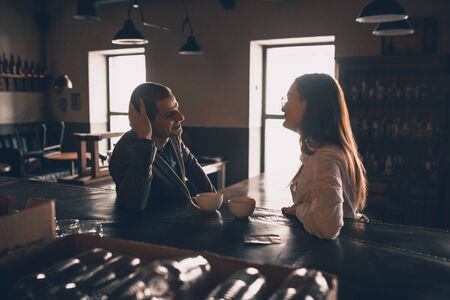 Cheerful caucasian man and woman talking, enjoying at the coffee shop, cafe, bar. Couple or friends, business partners drinking toghether, having a date, romantic. Communication, relations concept. Foto de archivo