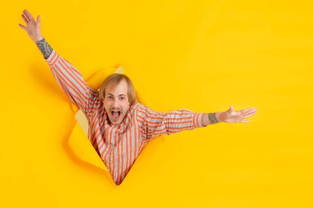 Surprising greeting. Cheerful caucasian young man poses in torn yellow paper background, emotional and expressive. Breaking on, breakthrought. Concept of human emotions, facial expression, sales, ad.