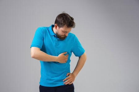 Young caucasian man suffers from side pain, feels sick, ill and weakness isolted on gray studio background. Symptoms of desease or unhealthy lifestyle. Sickness, ilness, sad and upset. Copyspace.