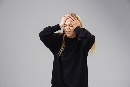 Young caucasian woman suffers from headache, fever, feels sick, ill and weakness isolted on gray studio background. Symptoms of desease or unhealthy lifestyle. Sickness, ilness, sad and upset. Copyspace.
