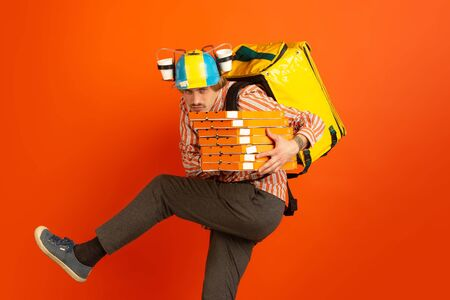 On the run. Emotions of caucasian deliveryman isolated on orange background. Contacless delivery service during quarantine. Man delivers food during isolation. Safety. Hurrying up. Copyspace. Stock Photo