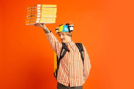 Graceful giving pizza boxes. Emotions of caucasian deliveryman isolated on orange background. Contacless delivery service during quarantine. Man delivers food during isolation. Safety. Hurrying up. Foto de archivo