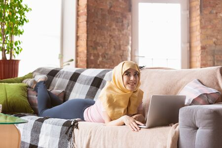A pretty young muslim woman at home during quarantine and self-insulation. Arabian female model spending time useful being isolated. Concept of healthcare, communication, education during pandemic. Banco de Imagens