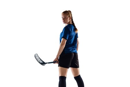 Floorball female player isolated on white studio background. Action and motion, movement, healthy lifestyle and overcoming concept. Young caucasian woman in sportwear training, practicing the game.