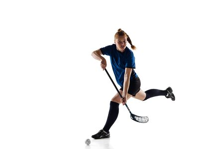 Floorball female player isolated on white studio background. Action and motion, movement, healthy lifestyle and overcoming concept. Young caucasian woman in sportwear training, practicing the game. Reklamní fotografie