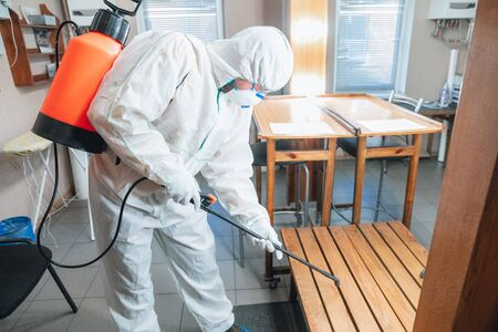 Coronavirus Pandemic. A disinfector in a protective suit and mask sprays disinfectants in house or office. Protection against COVID-19 disease. Prevention of spreding pneumonia virus with surfaces. Reklamní fotografie