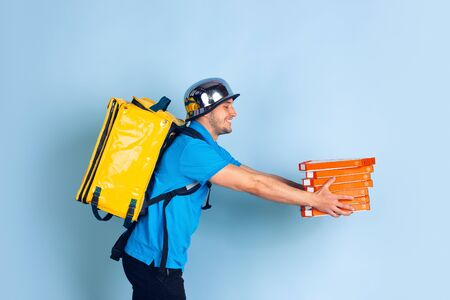 Giving pizza. Emotions of caucasian deliveryman isolated on blue background. Contacless delivery service during quarantine. Man delivers food during isolation. Safety. Hurrying up. Looks fun.