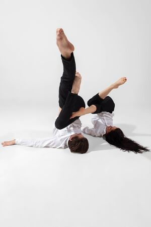 Young and graceful ballet dancers in minimal black style isolated on white studio background. Art, motion, action, flexibility, inspiration concept. Flexible caucasian ballet dancers, weightless jumps.