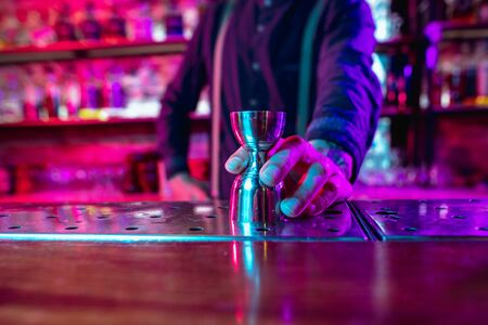 Close up of professional barman finishes preparation of alcoholic cocktail in multicolored neon light