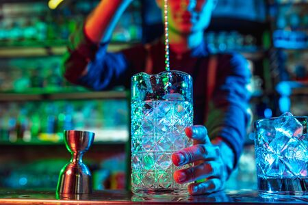 Close up of professional barman finishes preparation of alcoholic cocktail in multicolored neon light, gives it to client. Entertainment, drinks, service concept. Modern bar, trendy neoned colors.