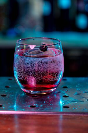 Close up of alcoholic cocktail, beverage, drink, prepared by professional barman in multicolored neon light. Entertainment, drinks, service concept. Modern bar, trendy neoned colors, copyspace.