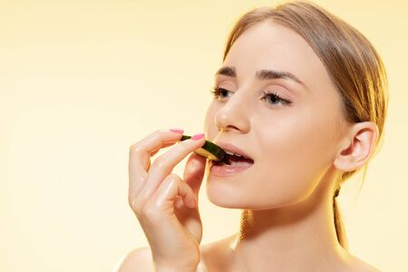 Close up of beautiful young woman with cucumber slice on yellow background. Concept of cosmetics, makeup, natural and eco treatment, skin care. Shiny and healthy skin, fashion, healthcare.