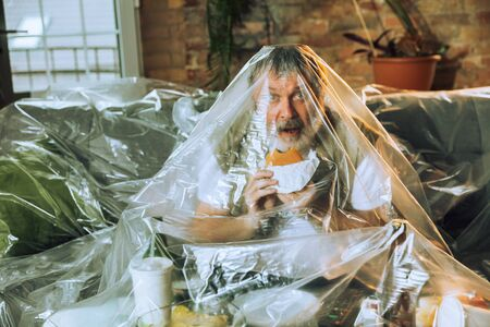 Senior man covered with plastic, eating fast food - environmental pollution by people concept. Eco campaign. Weve polluted the planet so much that no longer notice it. Unhealthy, garbage, problem.