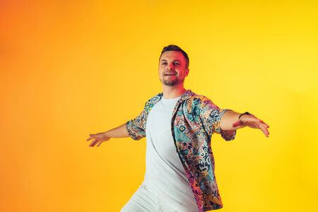 Young caucasian musician in casual dancing on gradient yellow background in neon light. Concept of music, hobby, festival. Joyful party host, DJ, stand upper, dancer. Colorful portrait of artist.