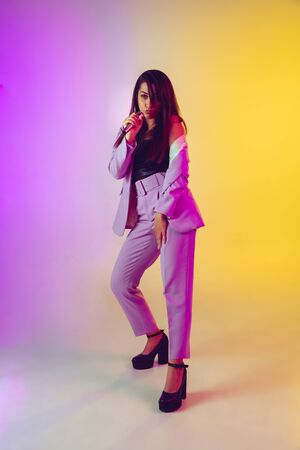 Caucasian female singer portrait isolated on gradient studio background in neon light. Beautiful female model in pink wear with microphone. Concept of human emotions, facial expression, ad, music, art. Stock Photo