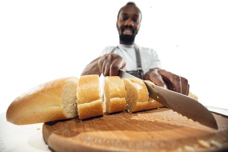 Amazing african-american man preparing unbelievable food with action, details and bright emotions, professional cook isolated on white studio background. Modern kitchen, artwork. Close up, wide angle. 免版税图像