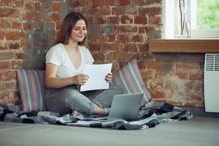 Young woman working or studying at home, looking on computer screen, monitor. Copyspace for your ad. Finance, business, work, gadgets and tech concept. Freelance, education, remote work.