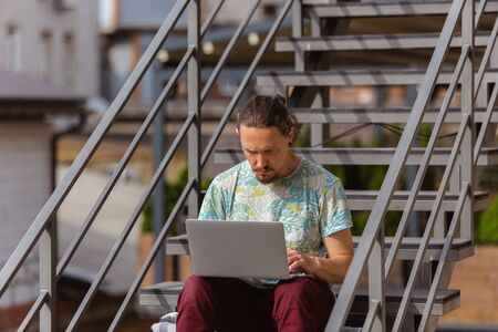 Typing. Young man, businessman working outdoors concentrated, looking on laptop screen, monitor. Copyspace for your ad. Finance, business, work, gadgets and tech concept. Freelance, remote worker.