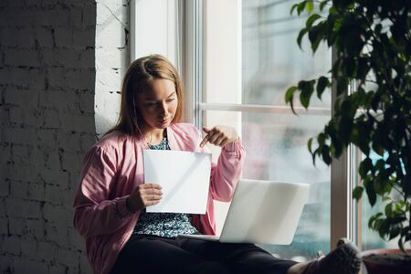 Showing. Young woman working or studying at home, showing whiteboard, white sheet. Copyspace for your ad. Finance, business, work, gadgets and tech concept. Freelance, education, remote work.